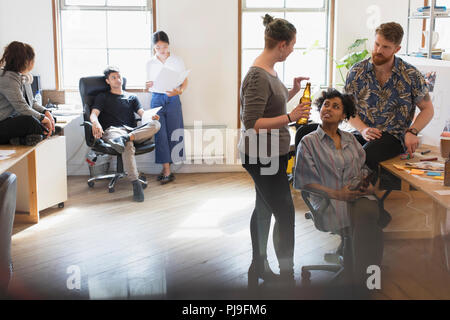Creative business people drinking beer and talking in office - Stock Image