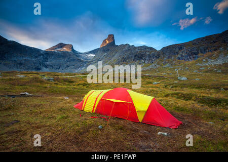 Red and yellow tent in Vengedalen valley below the peak Romsdalshorn (upper center), Møre og Romsdal, Norway. - Stock Image