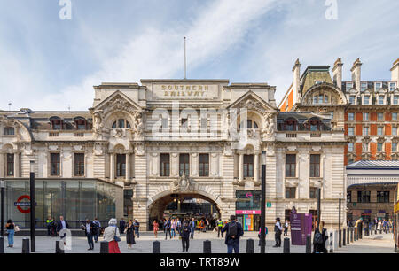 Exterior façade of London Victoria Station, City of Westminster, London, UK, a major transport terminus and hub on a sunny morning with blue sky - Stock Image