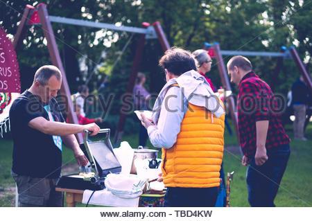 Two adult men preparing different sweet snacks - Stock Image