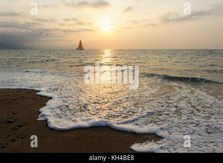 Sailboat sunset is a sailboat sailing along the ocean at sunset. - Stock Image