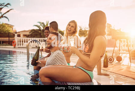 Group of happy friends making a pool party at sunset - Young people laughing and having fun drinking champagne in vacation - Stock Image