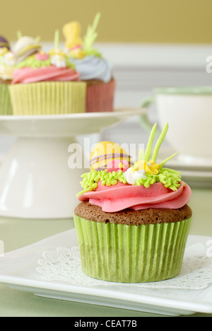 Easter decorated chocolate cupcakes with vanilla frosting and sugar decorations - Stock Image