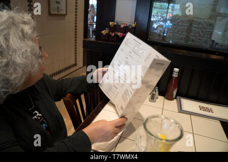 Reading the menu at the 2nd Avenue Deli on the Upper East Side of Manhattan. May 8, 2019 - Stock Image