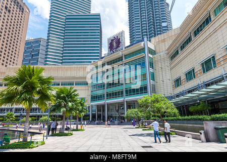KUALA LUMPUR, MALAYSIA - AUGUST 3: People walks in KLCC park and Suria KLCC shopping mall on the background on August - Stock Image