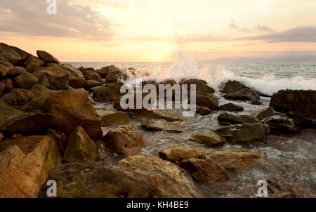 Sunset ocean wave is an ocean seascape at sunset with a wave breaking nd crashing on shore. - Stock Image