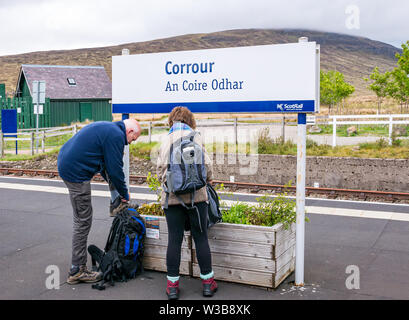 ScotRail Corrour rural train station platform name sign with walkers on West Highland railway line, Scottish Highlands, Scotland, UK - Stock Image