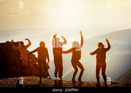 Happy friends dancing on sunset mountain - Stock Image