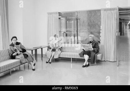 Three women read their Chicago Sun Times newspapers in the lobby of an office building in Chicago, ca. 1960. - Stock Image
