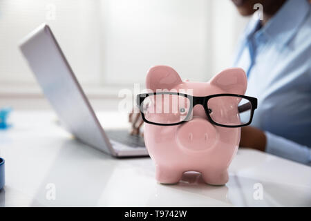 Close-up Of Pink Piggy Bank In Front Of A Business Person Using Laptop At Workplace - Stock Image