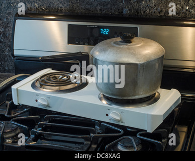 electric hot plate on top of gas range - Stock Image