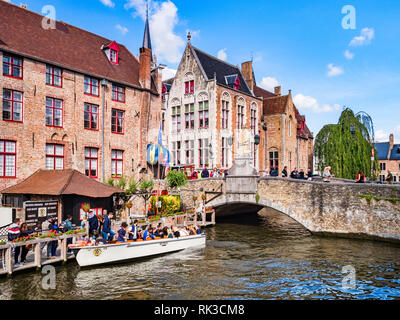 25 September 2018: Bruges, Belgium - Tourists boarding a tour boat on the canal by the Wollestraat Bridge in Bruges. - Stock Image