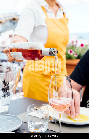 Waitress pouring wine into wineglass - Stock Image
