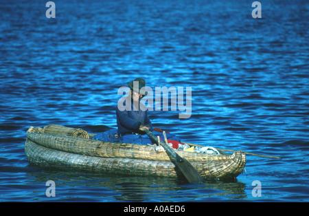 Uros Indigineous Peruvian Rowing a Reed Boat, Lake Titicaca, Peru - Stock Image