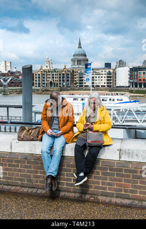 Tourists texting on their mobile phones and sitting on a wall on the South Bank in London with the dome of St Pauls Cathedral in the background. - Stock Image
