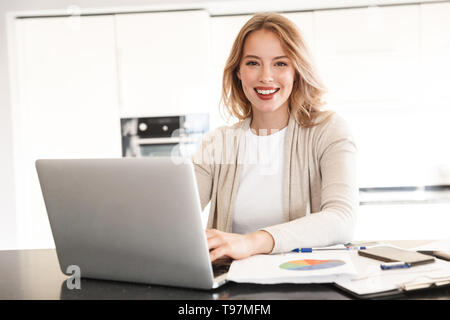 Image of a beautiful blonde woman posing sitting indoors at home using laptop computer. - Stock Image