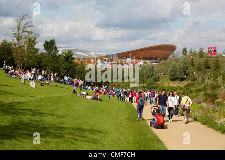 People sitting on lawns in sunshine on a sunny day with Velodrome at Olympic Park, London 2012 Olympic Games site, - Stock Image