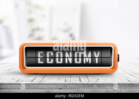 Economy word on an analog device in a bright home on a wooden desk - Stock Image