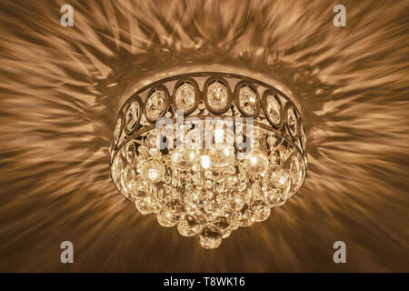 Crystal ceiling chandelier glowing and iridescent. - Stock Image