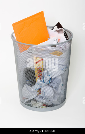 Waste paper basket filled with rubbish. - Stock Image