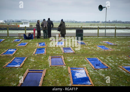 Deck chairs covered in ice and frozen to the ground at the 76th Goodwood Members Meeting. - Stock Image