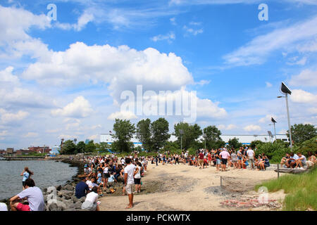 People resting on an East River Park beach during Smorgasburg in Williamsburg, Brooklyn on JULY 8th, 2017 in New York, USA. (Photo by Wojciech Migda) - Stock Image