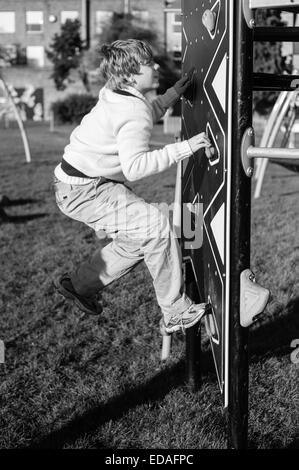 Boy climbing a climbing wall in a playground in Daventry, Northamptonshire during the winter - Stock Image