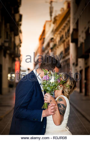 Newlywed couple kiss in the middle of an alley in a European city - Stock Image