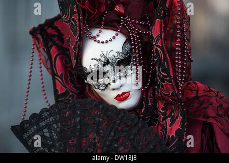 Venice, Italy. 25th Feb, 2014. A portrait of a white masked Carnivale attendee in a deep red costume holding a black fan. Venice Carnivale - Tuesday 25th February. Credit:  MeonStock/Alamy Live News - Stock Image
