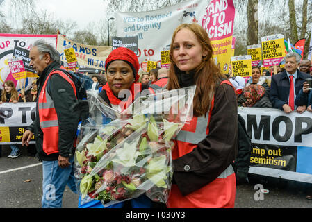 London, UK. 16th March 2019. Women hold a wreath at the front of the march. Thousands march through London on UN Anti-Racism day to say 'No to Racism, No to Fascism' and that 'Refugees Are Welcome Here', to show solidarity with the victims of racist attacks including yesterdays Christchurch mosque attack and to oppose Islamophobic hate crimes and racist policies in the UK and elsewhere. The marchers met in Park Lane where there were a number of speeches before marching to a rally in Whitehall. Marches took place in other cities around the world including Glasgow and Cardiff. Peter Marshall/Ala - Stock Image