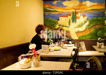 Two women in a café having lunch with a wall decoration of a Tuscan scene - Stock Image