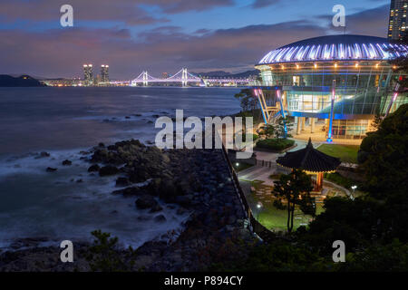 Seascape in Busan, South Korea, with APEC building in the foreground and city lights  in the far horizon. - Stock Image
