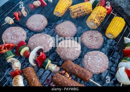 Burgers, lamb kebabs and skewers of vegetables cooking in a barbecue. - Stock Image