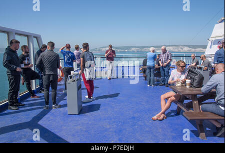 People sunning themselves on open rear deck of P&O Car Ferry leaving Dover with white cliffs in background - Stock Image