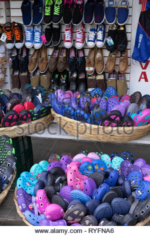 A street market stall is well stocked with plastic shoes before the rainy season begins. - Stock Image