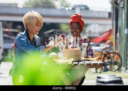 Happy young women friends enjoying dim sum lunch at sunny sidewalk cafe - Stock Image