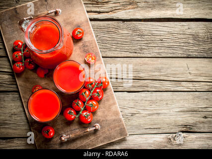 Fresh tomato juice. On a wooden background. - Stock Image