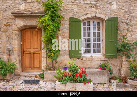 Street view of quaint old stone house facade with a wooden door, shuttered french window, and colorful potted plants. Provence, France. - Stock Image
