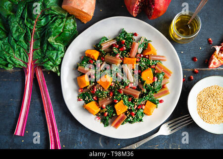 Boiled swiss chard with sweet potato, pomegranate and sesame seeds on a blue wooden background. Top view - Stock Image