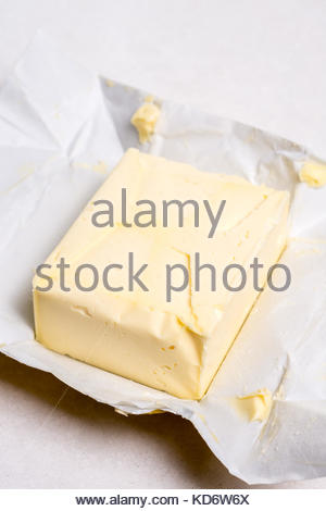 Slice of butter on the paper above white marble table. - Stock Image