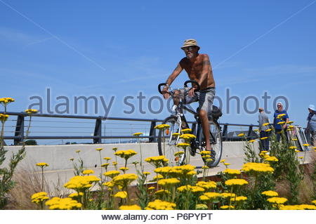 Littlehampton, UK. Monday 2nd July 2018. Shirtless man cycling along the promenade on another very warm and humid morning in Littlehampton, on the South Coast. Credit: Geoff Smith / Alamy Live News. - Stock Image