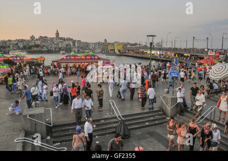 People walk on the Golden Horn waterfront by Galata bridge in Eminönü on a summer's evening.  The - Stock Image