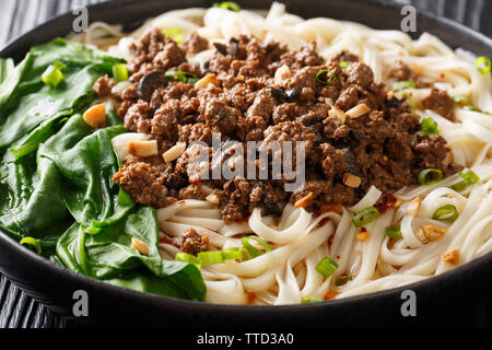 Sichuan Dan Dan Noodles with minced meat and greens closeup in a plate on the table. horizontal - Stock Image