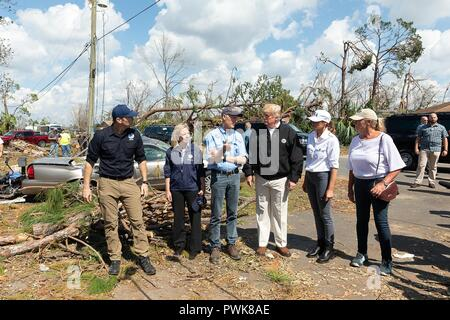 Panama City, Florida, USA. 15th Oct 2018. U.S President Donald Trump during a tour of damage in the aftermath of Hurricane Michael October 15, 2018 in Lynn Haven, Florida. Standing with the president from left to right are: FEMA Administrator Brock Long, Homeland Security Secretary Kirstjen Nielsen, Florida Gov. Rick Scott, President Donald Trump, First Lady Melania Trump and First Lady of Florida Ann Scott. Credit: Planetpix/Alamy Live News - Stock Image
