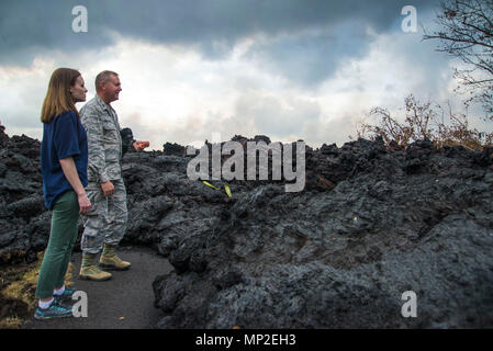 FEMA employee Meghan Breitenbach and U.S. Air Force Lieutenant Colonel Chuck Anthony view a portion of the hardened lava flow spewing from the Kilauea volcanic eruption May 18, 2018 in Pahoa, Hawaii. The recent eruption continues destroying homes, forcing evacuations and spewing lava and poison gas on the Big Island of Hawaii. - Stock Image