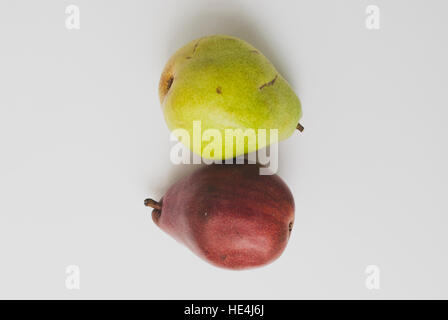 Purple and green pears on a white background - Stock Image