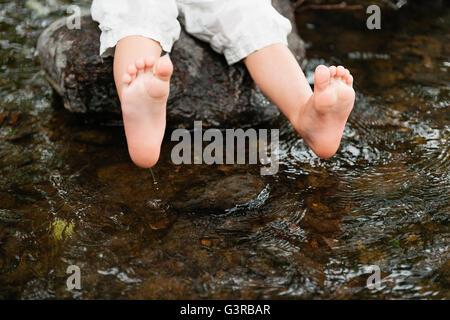 Sweden, Vastmanland, Baby boy (18-23 months) dipping feet in water - Stock Image