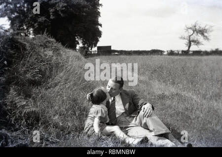 11950s, historical, father wearing a jacket and tile giving his young daughter an affectionate little kiss outdoors on a day-out in the countryside. - Stock Image