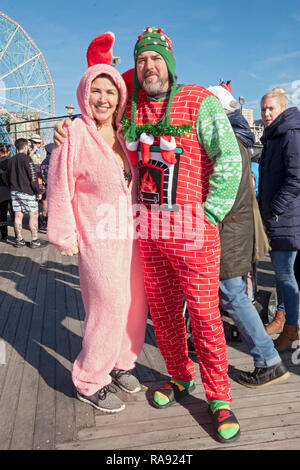 A couple on the boardwalk prior to the annual Polar Bear Club New Year's Day swim - her in a bunny outfit & him in an ugly Christmas hat and fireplace. - Stock Image