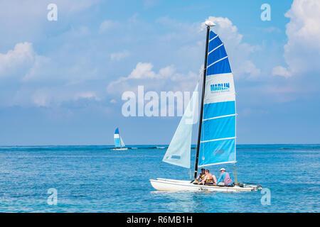 Tourists enjoy sailing on a small catamaran at a resort in Cuba - Stock Image